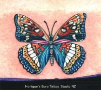 Super colourful butterfly tattoo on tail base